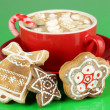 Cup of coffee with Christmas sweetness on green background - Photo