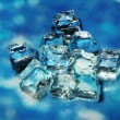 Ice cubes on color background - Stock Photo