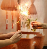 Beautiful sparklers in woman hands on room background — Stock Photo