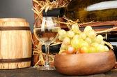 Holzetui mit weinflaschen, lauf, weinglas und weintraube auf holztisch auf grauen hintergrund — Stockfoto