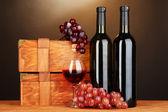 Dřevěný případy s lahví vína na dřevěný stůl na hnědé pozadí — Stock fotografie