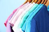休闲衬衫木衣架,在蓝色背景上的各种 — 图库照片