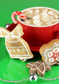 Cup of coffee with Christmas sweetness on green background — Photo