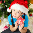 Little girl holding gift box near christmas tree — Stock Photo #18132803