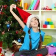Little girl in red cap sitting near christmas tree — Stock Photo