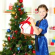 Little girl holding gift box near christmas tree — Stock Photo #18132843