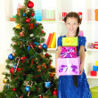Little girl holding gift box near christmas tree — Stock Photo #18132855