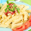 Rigatoni pasta dish with tomato sauce on blue wooden table close up — Stok fotoğraf
