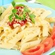 Rigatoni pasta dish with tomato sauce on blue wooden table close up — Стоковая фотография