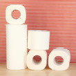 Rolls of toilet paper on striped red background — Stock Photo #18133323