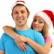 Photo: Loving couple in Santa hats isolated on white