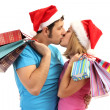 Young couple in Santa hats shopping and holding many shopping bags isolated on white — Stock Photo #18133357