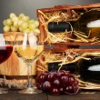 Wooden case with wine bottles, barrel, wineglasses and grape on wooden table on grey background — Stock Photo