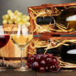Wooden case with wine bottles, barrel, wineglasses and grape on wooden table on grey background - Stock Photo