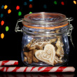 Tasty cookies in glass bottle on blur lights background — Stock Photo #18133517