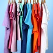 Variety of casual shirts on wooden hangers,on blue background — Stock Photo #18133535
