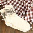 Warm knitted socks on wooden table close-up - Stock Photo