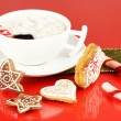 Cup of coffee with Christmas sweetness on red background — Stock Photo #18133547