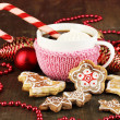 Cup of coffee with Christmas sweetness on wooden table on red bokeh background — Stock Photo #18133553