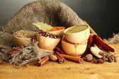 Ciotole e cucchiai con spezie, sul tavolo di legno su sfondo grigio — Foto Stock