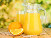 Full glass and jug of orange juice and oranges on wooden table outdoor — Stock Photo