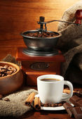 Coffee grinder and cup of coffee on brown wooden background — Stock Photo