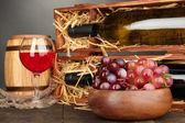 şarap şişeleri, varil, bardağı ve gri arka plan üzerinde ahşap masa üstünde üzüm ile ahşap durum — Stok fotoğraf
