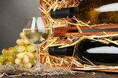 şarap şişeleri, bardağı ve gri arka plan üzerinde ahşap masa üstünde üzüm ile ahşap durum — Stok fotoğraf