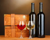 Wooden cases with wine bottles on wooden table on brown background — Stockfoto