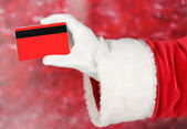 Santa Claus hand holding red credit card on red background — Stock Photo