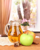 Full jug of apple juice and apple on wooden table on bright background — Stockfoto