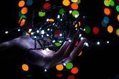 Vánoční osvětlení v ruce na pozadí světla rozostření — Stock fotografie