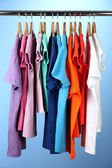 Variety of casual shirts on wooden hangers,on blue background — Stok fotoğraf