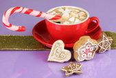 Cup of coffee with Christmas sweetness on purple background — Stock Photo