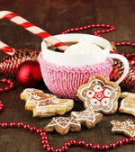 Cup of coffee with Christmas sweetness on wooden table on red bokeh background — Stock Photo