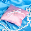 Wedding rings on satin pillow on blue cloth background - Stockfoto