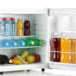 Mini fridge full of bottles of juice, soda and fruit isolated on white — Stock Photo