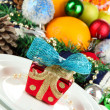 Stock Photo: Small Christmas gift on plate on serving Christmas table background close-up