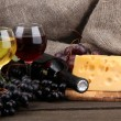 Bottle and glasses of wine, cheese and grapes on grey background — Stock Photo #18169739