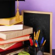 Books and magister cap against school board on wooden table on purple background — Stock Photo