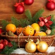 Christmas composition in basket with oranges and fir tree, on wooden background - Stok fotoğraf