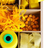 Yellow thread and material for handicrafts in box isolated on white — Stock Photo