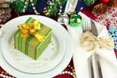 Small Christmas gift on plate on serving Christmas table background close-up — Стоковое фото