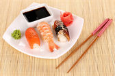 Delicious sushi served on plate on bamboo mat — Stock Photo