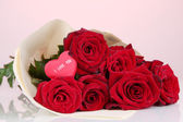 Beautiful bouquet of red roses with valentine on red background — Stock Photo