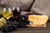 Bottle and glasses of wine, cheese and grapes on grey background — Stock Photo