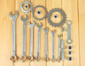Machine gear, metal cogwheels, nuts and bolts on wooden background — Stock Photo