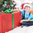 Child in Santa hat sits near Christmas tree with big gift in hands — Stock Photo