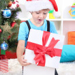 Little boy open his gifts near Christmas tree — Stock Photo