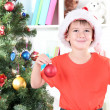 Little boy in Santa hat decorates Christmas tree in room — Stock Photo #18170035